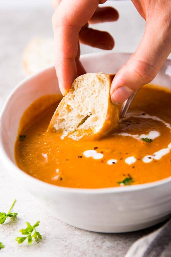 Dipping baguette in tomato soup
