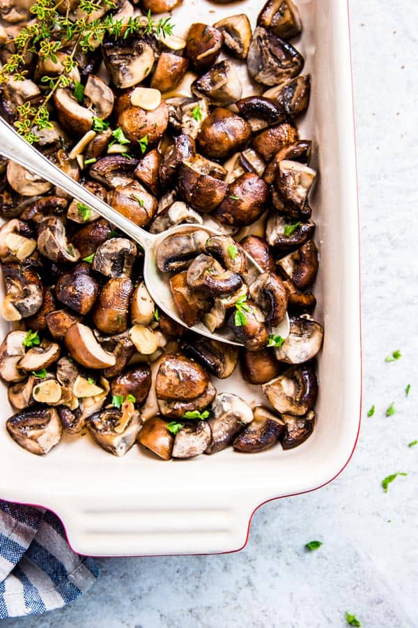 Garlic Butter Mushrooms in a Le Creuset casserole dish with a spoon.