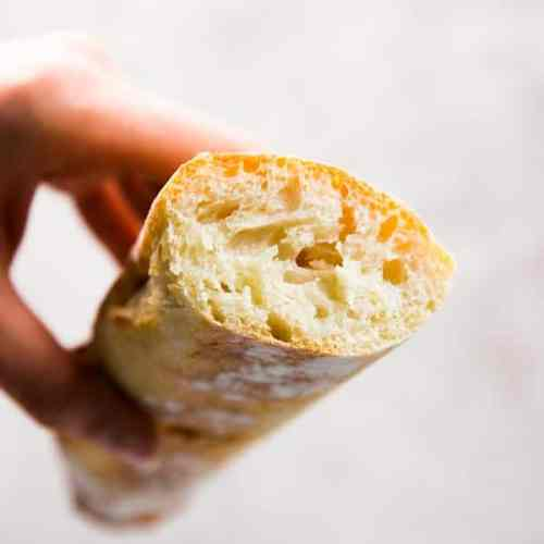 Holding a sliced homemade French bread.