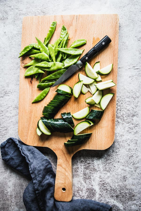 Sliced zucchini and sugar snap peas on a wooden board with a knife and a black towel.