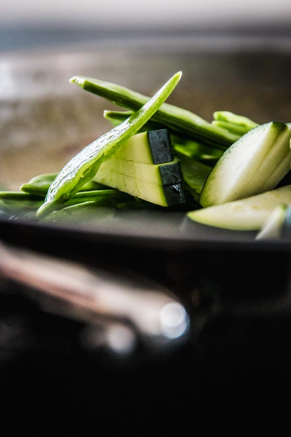 Zucchini and sugar snap peas in a skillet.