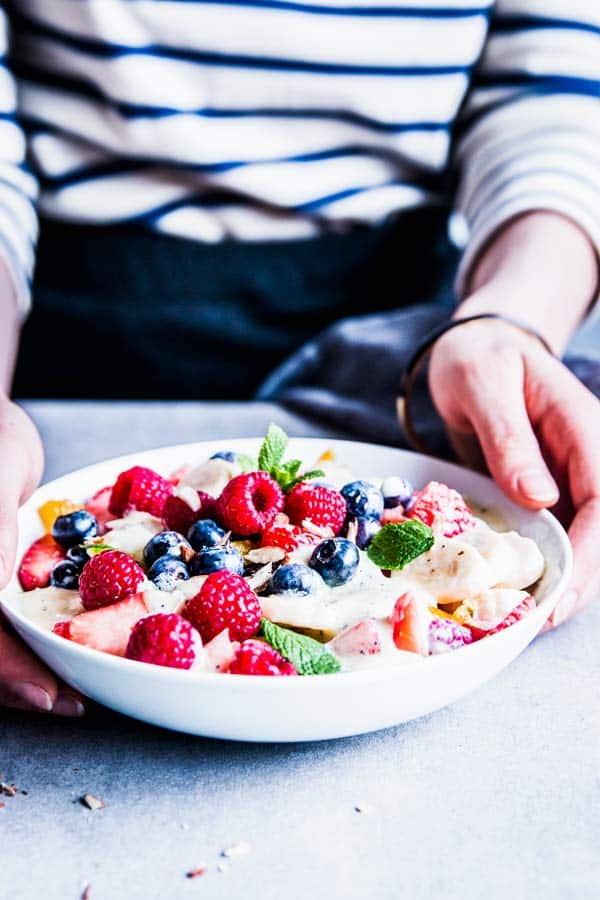 Woman in a striped t-shirt serving creamy fruit salad.
