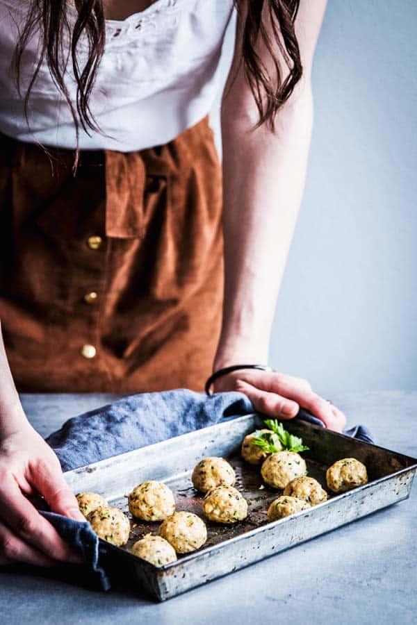 Woman serving a tray of baked Greek Turkey Meatballs.