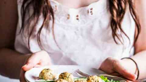 Woman in a white top and tan skirt holding a plate of greek turkey meatballs.