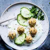 Greek turkey meatballs on a white plate with yogurt, cucumber slices and a fork. Black napkin next to it.