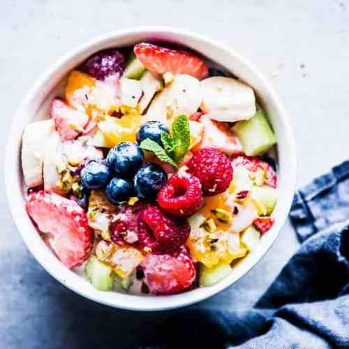 Greek Yogurt Fruit Salad in a white bowl with mint and a dark napkin.