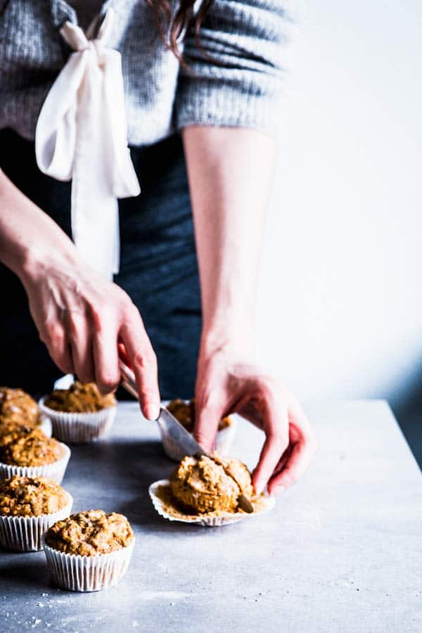Woman cutting a healthy carrot muffin in half.