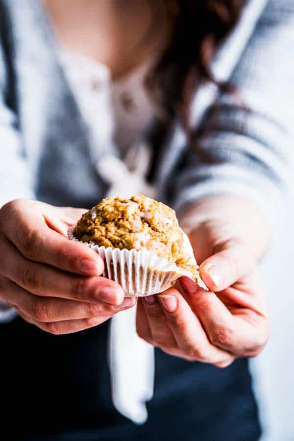 Woman holding out a healthy carrot muffin.
