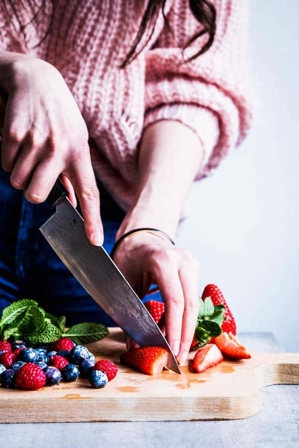 Woman slicing strawberries for a fruit salad.