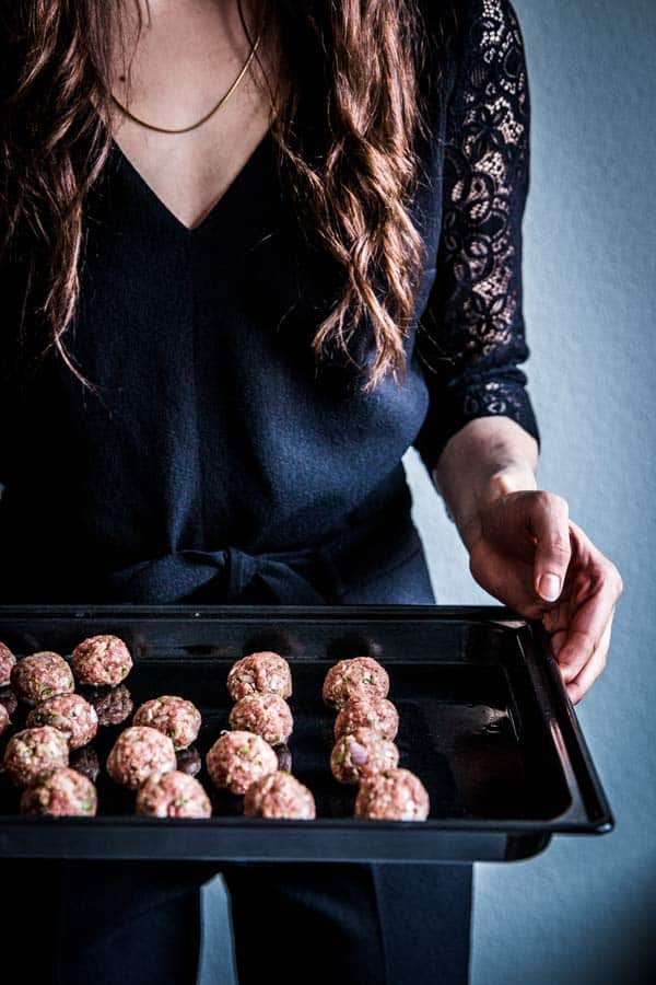 Woman in a black jumpsuit, holding a sheet pan full of homemade meatballs.