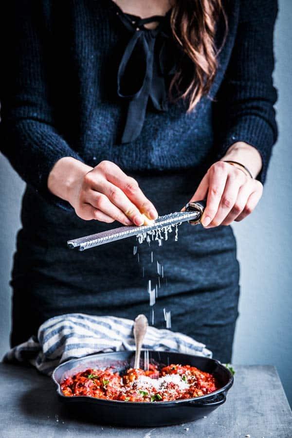 Woman in a black dress grating parmesan on top of Italian meatballs.