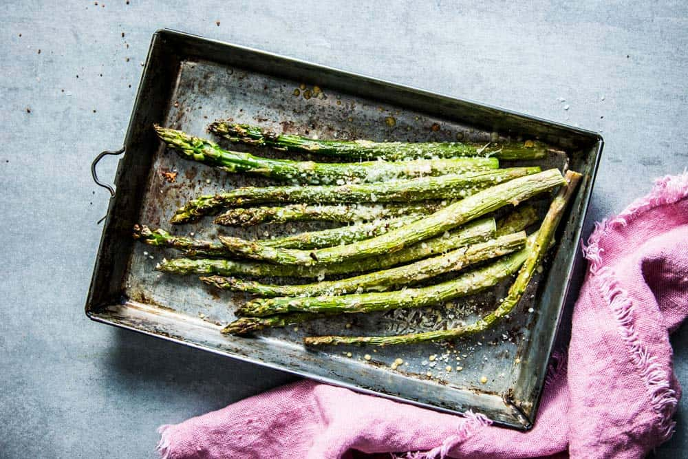 Garlic Parmesan Roasted Asparagus on a sheet pan, next to a pink napkin.