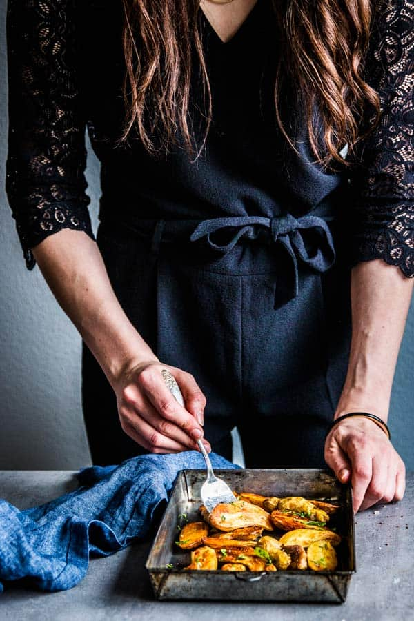 Women in a black jumpsuit serving roasted fingerling potatoes.