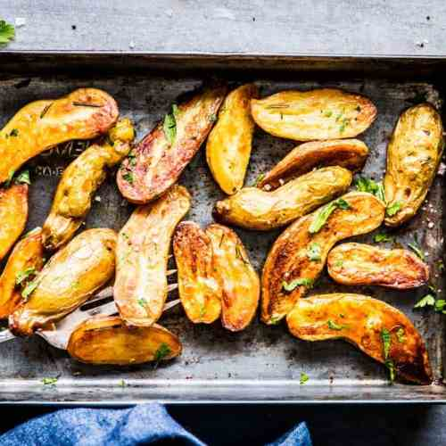 Roasted Fingerling Potatoes on a sheet pan with fresh parsley, next to a blue napkin.