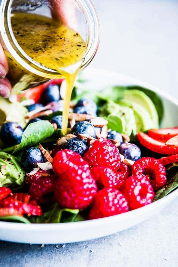 Pouring White Balsamic Vinaigrette over Spinach Avocado Salad.