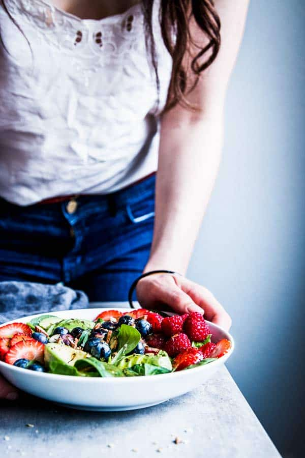 Woman in a white top serving a bowl of Spinach Avocado Salad.