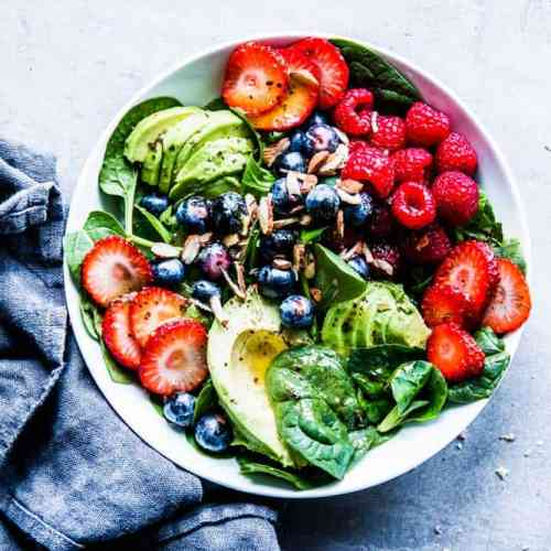 Spinach Avocado Salad in a white bowl with a black napkin.