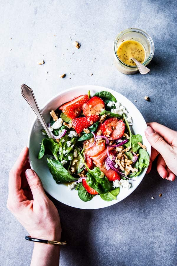 Hands placing a white bowl with spinach strawberry walnut salad on the table.