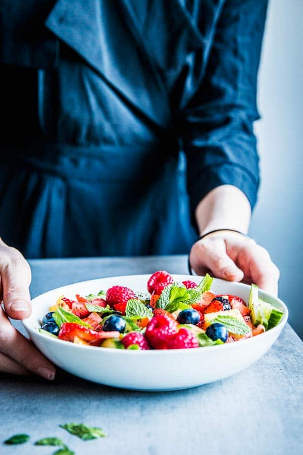Woman in a black dress placing a white bowl with summer fruit salad on the counter.