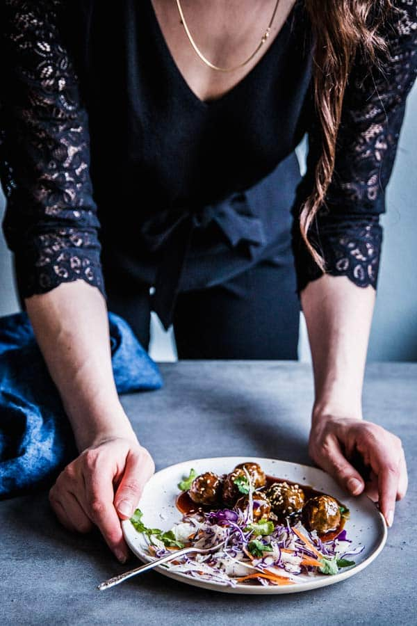 Woman in a black jumpsuit, serving a plate of teriyaki meatballs and coleslaw.
