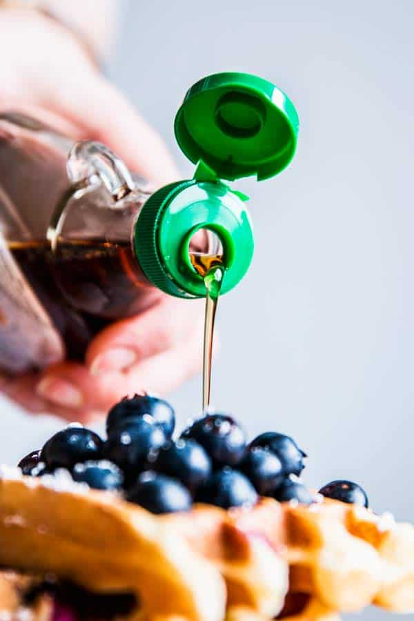 Pouring syrup over Blueberry Waffles.