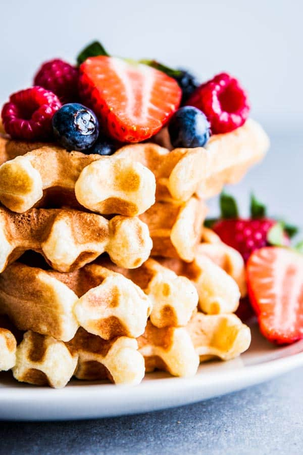 Close up photo of fluffy buttermilk waffles with berries.