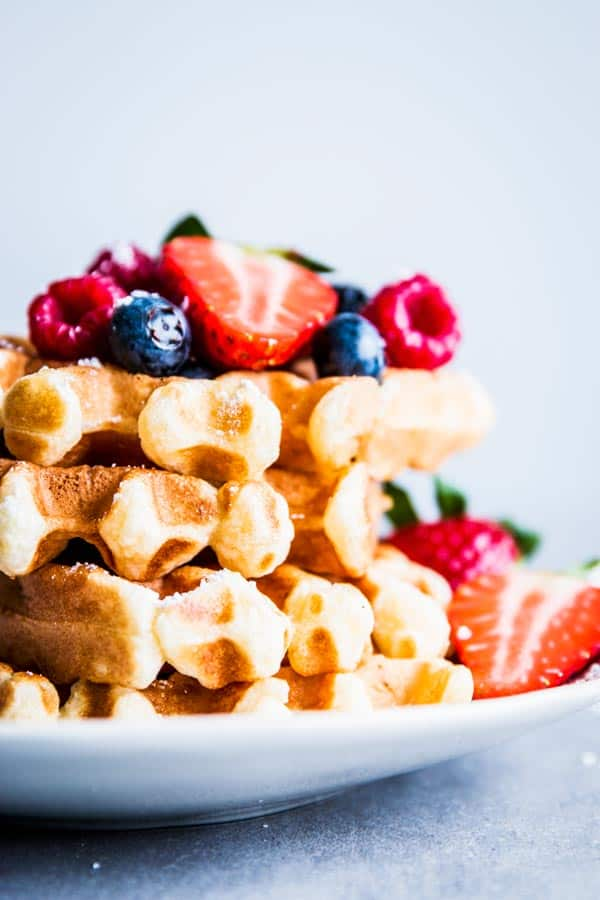 Stack of buttermilk waffles on a plate, topped with mixed berries.