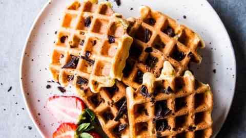 Chocolate chip waffles on a white plate with sliced strawberries.