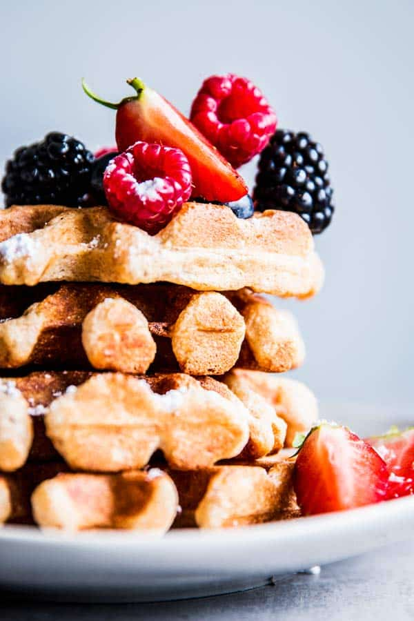 Stack of Fluffy Whole Wheat Waffles on a white plate, topped with fresh berries.