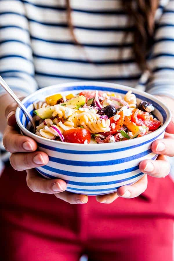 woman holding a bowl of greek pasta salad