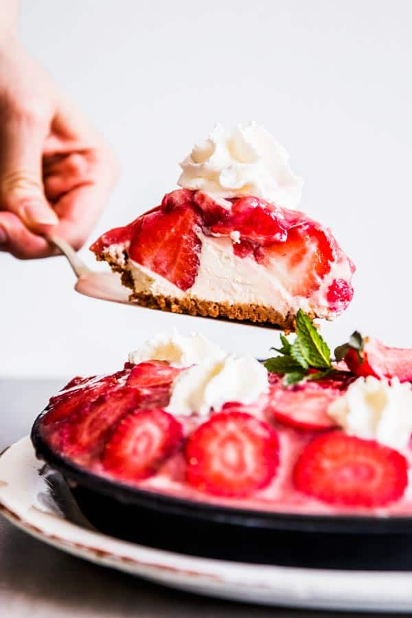 Scooping a slice of no bake strawberry pie.