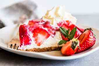 No Bake Strawberry Pie on a plate with fresh strawberries.