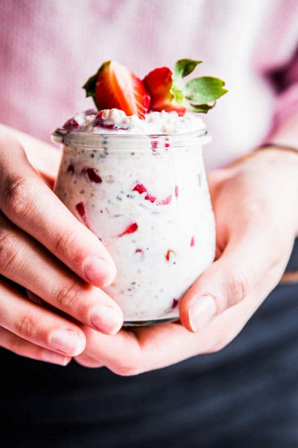 Woman holding a jar of vanilla strawberry overnight oats.