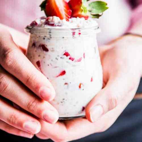Woman holding a jar of vanilla strawberry overnight oats.