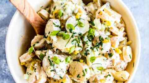 greek yogurt potato salad in a large bowl with a wooden spoon