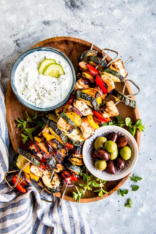 greek chicken kabobs on a wooden platter with tzatziki and olives