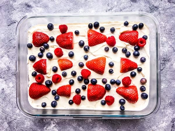 decorated triple berry no bake cake in a pan