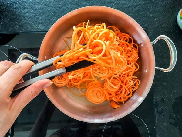 tossing raw sweet potato noodles in a hot skillet
