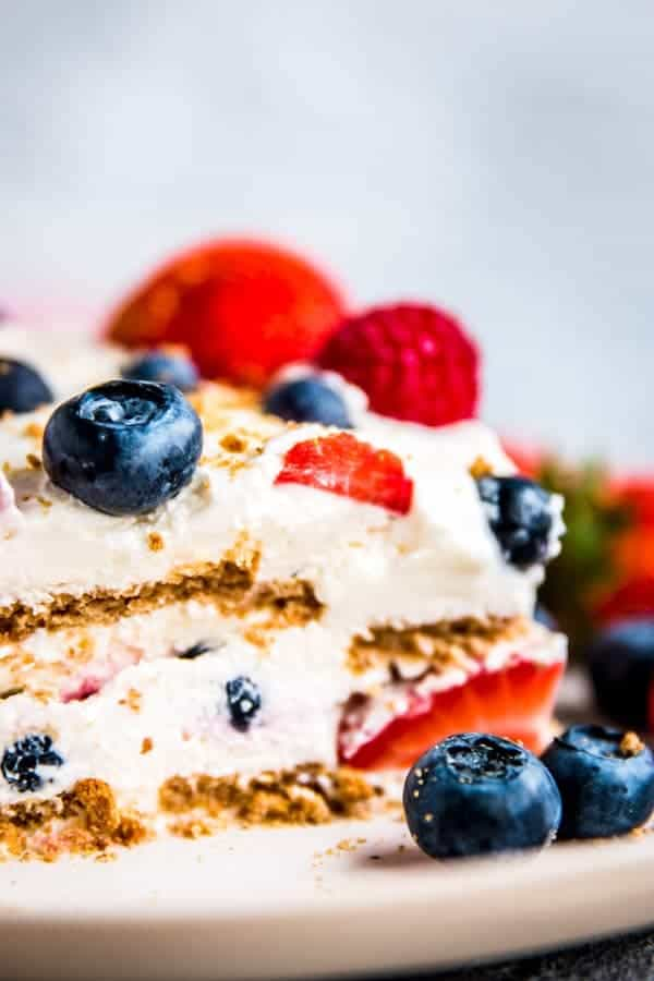 triple berry icebox cake on a plate with fresh berries