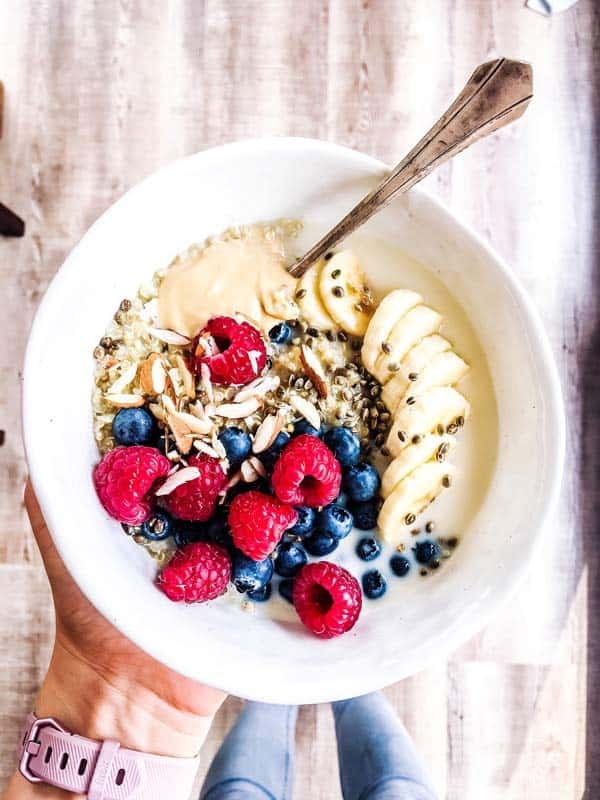 woman holding a white bowl with breakfast quinoa and berries