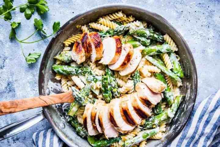chicken asparagus pasta in creamy sauce in a skillet