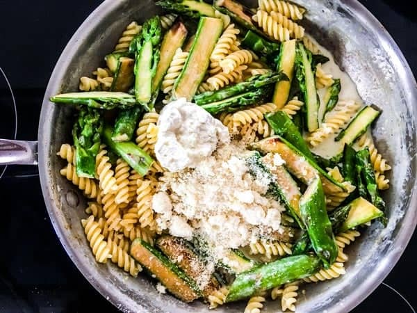 cheese and asparagus and pasta in creamy sauce in a skillet