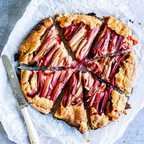 rhubarb galette slices on a piece of parchment paper with a knife