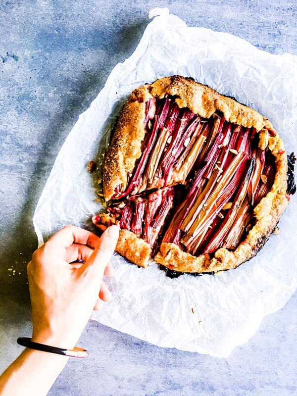 woman taking a slice of rhubarb galette