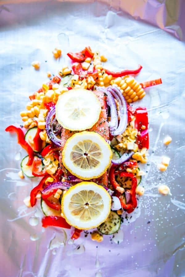 lemon, salmon, seasoning and veggies on foil for salmon foil packets