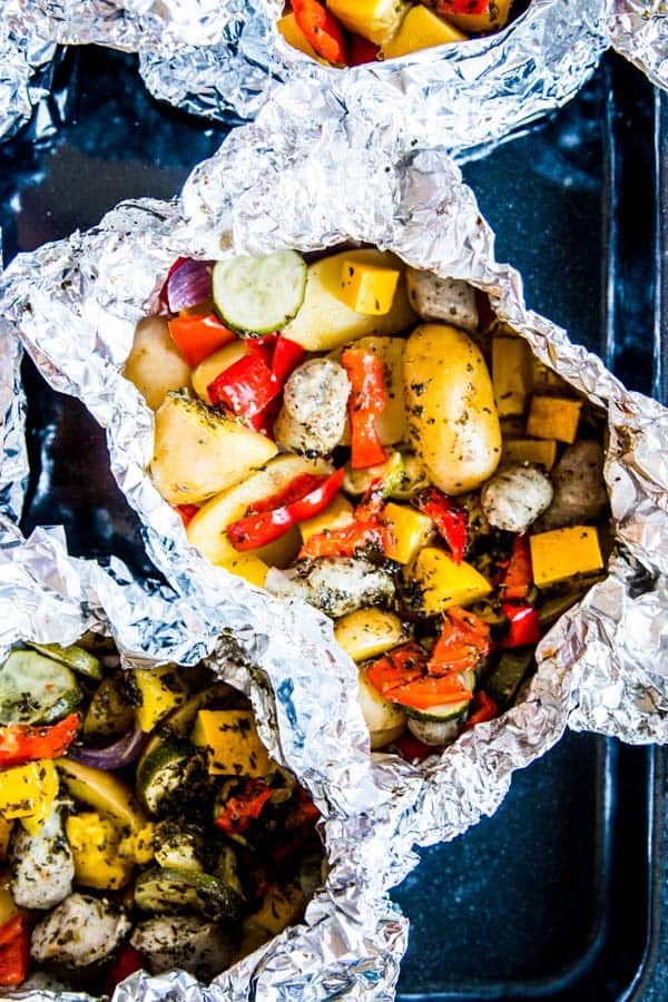 sausage and potato foil packet on a dark sheet pan