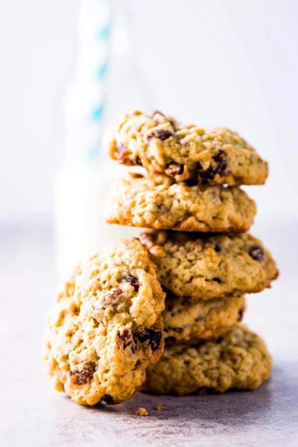 stack of oatmeal raisin cookies with a bottle of milk in the background