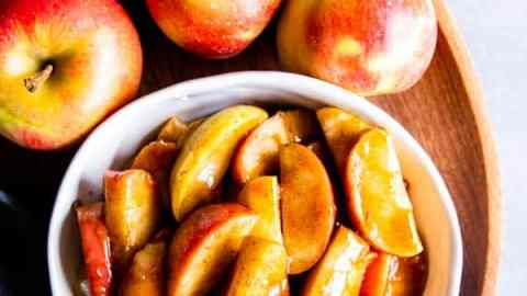 cinnamon apples in a white bowl with fresh apples around