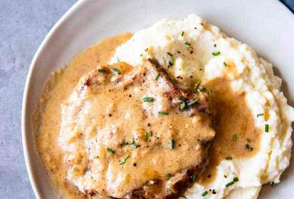 instant pot sour cream pork chops on a plate with mashed potatoes