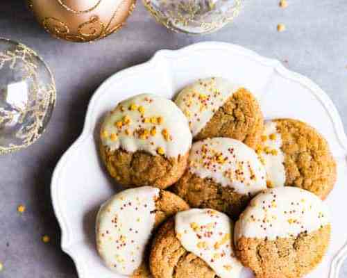 a plate with chewy gingersnap cookies next to Christmas ornaments